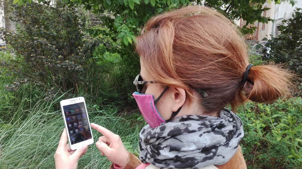 Femme masquée regardant une application